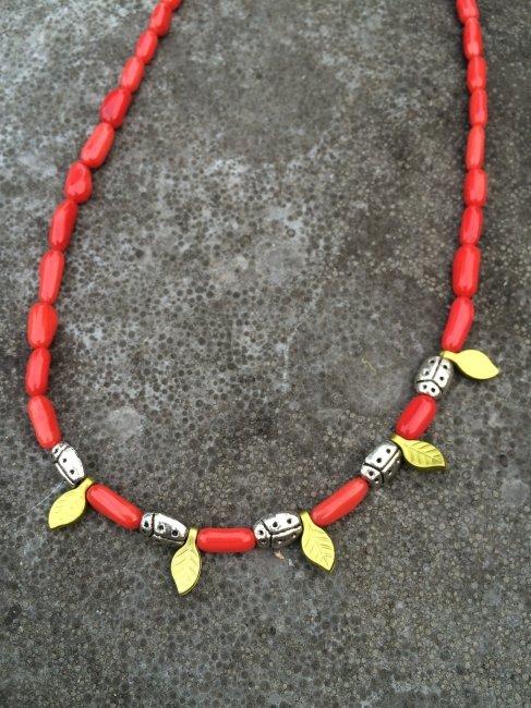 Ketting van rood koraal en lieveheersbeestjes op blaadjes