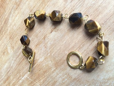 Prachtige armband met gefacetteerde tijgeroog afgewerkt op goudkleurig ijzerdraad