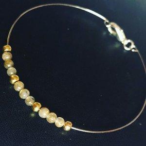 Fijne armband met kleine gefaceteerde labradoriet kralen op goudkleurig memorywire