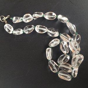 Ketting van helder bergkristal op donkergroen waskoord
